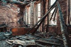 Hus för bränd tegelsten som är inre med bränt möblemang, förstört byggande rum efter brand inom royaltyfri bild
