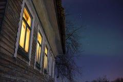 Hus för by för ryss för Closeupwindowsof hemtrevligt gammalt i den bittra förkylningen på vinternatten Fotografering för Bildbyråer