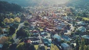 Hus för flyg- sikt i bostads- förorts- grannskaplandskap på solnedgånglinsen blossar
