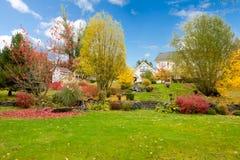 Hus för lantgård för vit häst amerikanskt under nedgång med grönt gräs. royaltyfria bilder