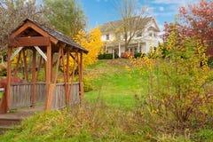 Hus för lantgård för vit häst amerikanskt under nedgång med grönt gräs. arkivbilder