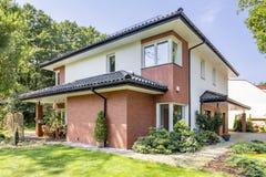 Hus för röd tegelsten med terrassen och grönt gräs och träd under su arkivbilder