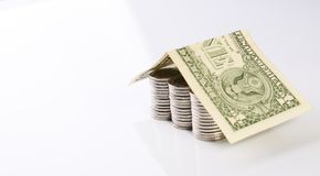 Hus från dollarkostnader på staplade mynt Arkivbilder