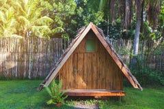 hus gjorde trä Bungalow med ett tak som göras av palmblad mot bakgrunden av ett staket av bambu och palmträd royaltyfria foton