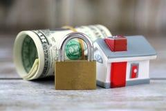 Hus, hänglås och dollar Begreppsmässig bild för aktieägare i fastighet och dollar Säkerhet av pengar och fastigheten Arkivbild
