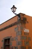 Hus i apelsin med trädörrar och det kända tecknet för gata Arkivbild