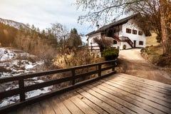 Hus i bergen, snön och träbron hemtrevlig kojabergöverkant Arkivbild