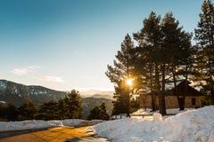 Hus i bergen som täckas med snö på solnedgången Royaltyfri Fotografi