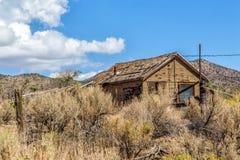 Hus i busksnår Arkivbild