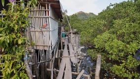 Hus i de filippinska slumkvarteren för fattigt folk Träbroar från plankor på högt vatten Armod av folk och familjer lager videofilmer