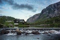 Hus i den norska sjön och dramatisk himmel arkivfoton