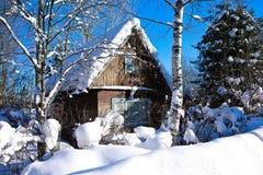 Hus i forestwinter bärsol Arkivfoto