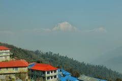 Hus i Ghorepani med Dhaulagiri når en höjdpunkt på bakgrund Royaltyfri Foto