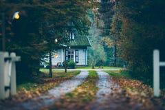 Hus i höstskog med körbanan på skymning Royaltyfri Foto