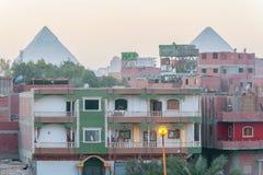 Hus i Kairo och pyramider av Giza på bakgrunden Royaltyfria Bilder