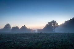 Hus i lettisk bygd på den dimmiga aftonen Arkivfoton