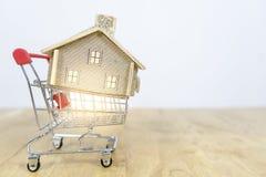 Hus i shoppingvagn, hur man blir en husägare, begrepp om online-shopping, köp- och försäljningshus royaltyfri bild