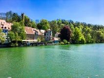 Hus i skog av sidan av sjön Arkivbilder