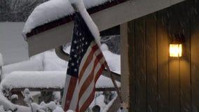 Hus i snö med amerikanska flagganflyg, i att falla för snö arkivfilmer