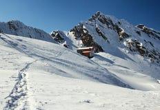 Hus i snöberg Arkivbild