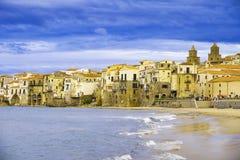 Hus längs shorelinen och domkyrkan i bakgrund Cefalu Sicilien royaltyfri bild