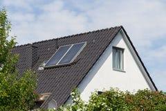 Hus med det svarta taket och sol- energi Arkivfoto
