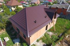 Hus med ett nytt metalltak Taket av det korrugerade arket Taklägga av krabb form för metallprofil arkivbilder