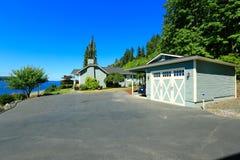 Hus med främre sikt för vatten, den stora körbanan och garaget Portspäckhuggare Royaltyfria Foton