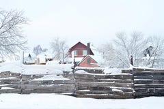Hus med land och byggnader som bakifrån täckas med snö, sikten staketet Sammansättning bakgrund royaltyfri foto