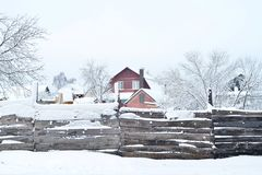 Hus med land och byggnader som bakifr?n t?ckas med sn?, sikten staketet Sammans?ttning bakgrund royaltyfri bild