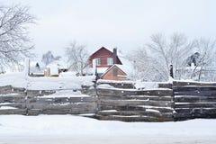 Hus med land och byggnader som bakifr?n t?ckas med sn?, sikten staketet Sammans?ttning bakgrund arkivbild