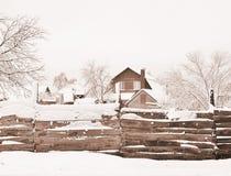 Hus med land och byggnader som bakifr?n t?ckas med sn?, sikten staketet Sammans?ttning bakgrund toning royaltyfria bilder