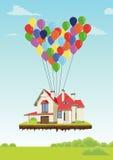 Hus med mångfärgade ballonger i form av hjärtaflyget i himmel över jordning Royaltyfri Bild