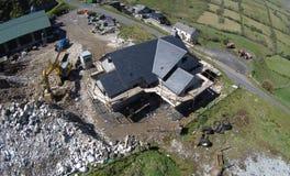 Hus med materialet till byggnadsst?llning runt om dess v?ggar som ?r byggt tak bredvid v?gen i bygden i Irland arkivbilder