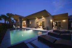 Hus med simbassängen på natten arkivfoton