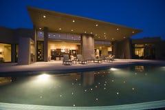 Hus med simbassängen på natten Arkivfoto