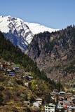 Hus med snö täckte berg i bakgrunden, Manali, Hima Arkivfoton