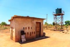 Hus med vattenbehållaren i en by i Afrika royaltyfria bilder