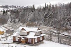 Hus nära bergfloden. Arkivbild