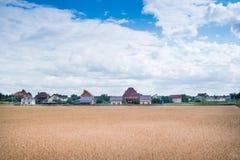 Hus nära fältet på sommarmiddagar royaltyfri fotografi