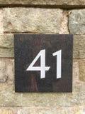 Hus nummer 41 på en granittjock skiva på en tegelstenvägg Royaltyfri Foto