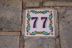 Hus nummer sjuttiosju 77 som målas på den keramiska tegelplattan i blått och svart med fransk liljamodellen från Sverige eller Be royaltyfri foto