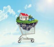 Hus och bil i shoppingvagn Arkivbilder
