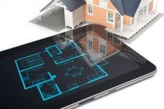 Hus och digital tablet Arkivfoto