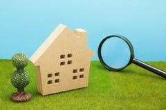 Hus och förstoringsglas på grönt gräs Arkivfoto