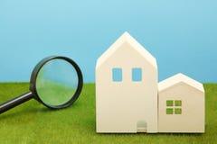 Hus och förstoringsglas på grönt gräs Royaltyfria Bilder