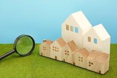 Hus och förstoringsglas på grönt gräs Arkivbild