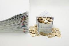 Hus och guld- mynt med högöverbelastningsdokumentet Arkivfoto