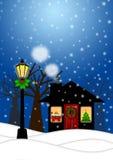 Hus- och lampstolpe i vinterjulplats Arkivfoton