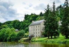 Hus och skog i flodstranden Gräsplan- och naturlandskap fotografering för bildbyråer